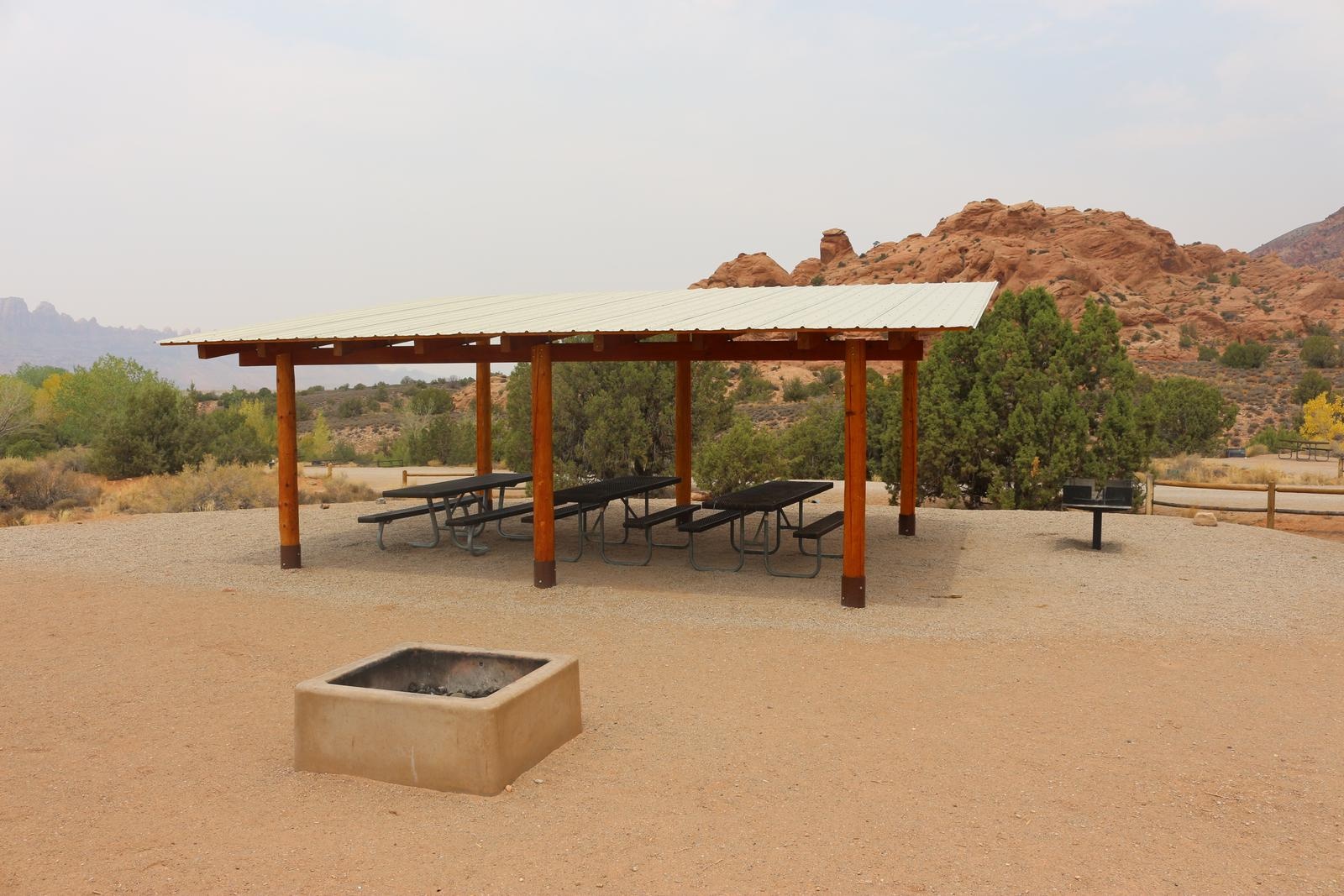 Ken's Lake Group Site B shade shelter, picnic tables, standing grill, and fire pit area.