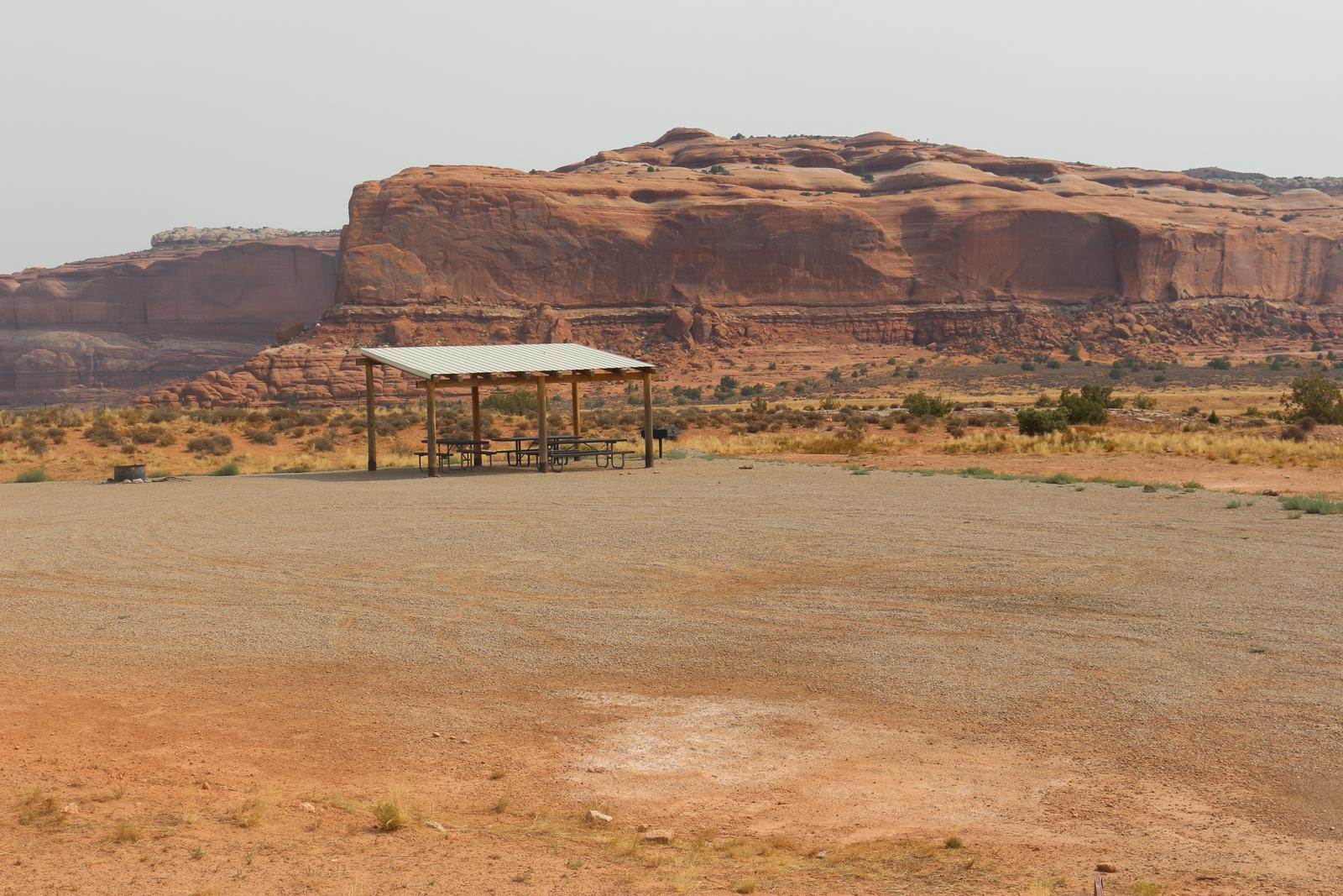 Lone Mesa Group Site B shade shelter and picnic tables. Red rock cliffs in the distance.
