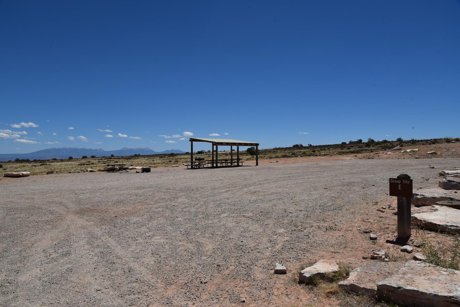 Lone Mesa Group Site C shade shelter, picnic tables, and parking area with the La Sal Mountains in the distance.