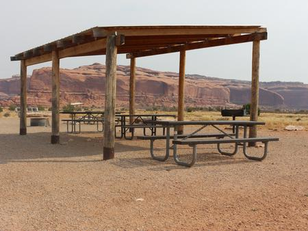Lone Mesa Group Site E shade shelter, picnic tables, and fire ring. Tall, red rock plateaus line the horizon.