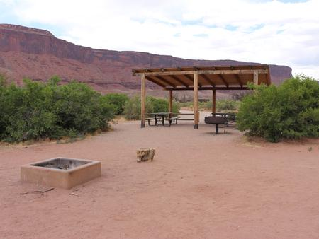A close up of the Lower Onion Creek Group Site A shade shelter, picnic tables, standing grill, and hang out area next to fire pit. Vegetation lines the area and in the distance are towering, red rock cliffs.