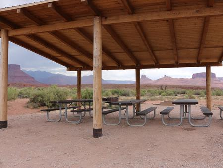 Close up of the Lower Onion Creek Group Site B shade shelter and picnic tables. Castleton and the La Sal Mountains can be seen in the distance.