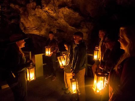 Historic Candle Light TourA tour group stand in a room of the cave all holding candle lanterns
