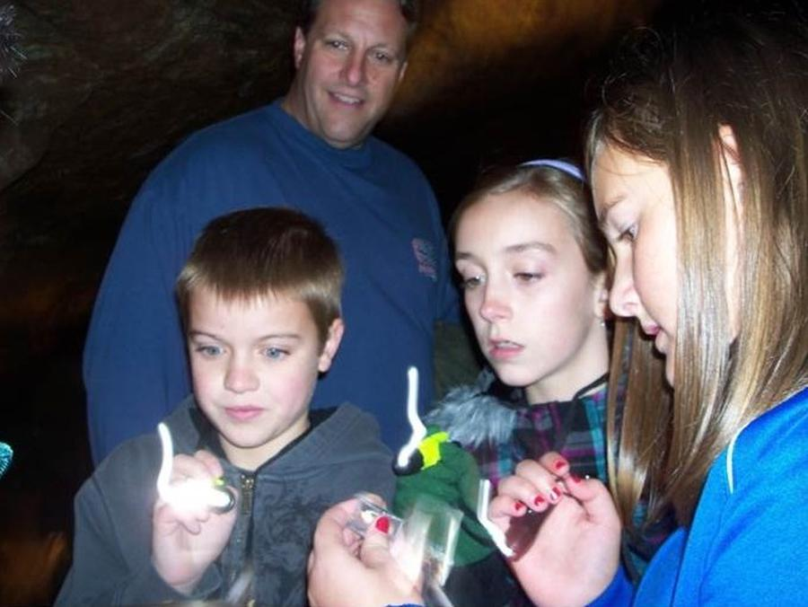 Kids and Family Discovery TourKids with flashlights exploring cave