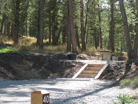 Site 40, campsite surrounded by pine trees, picnic table & fire ringSite 40