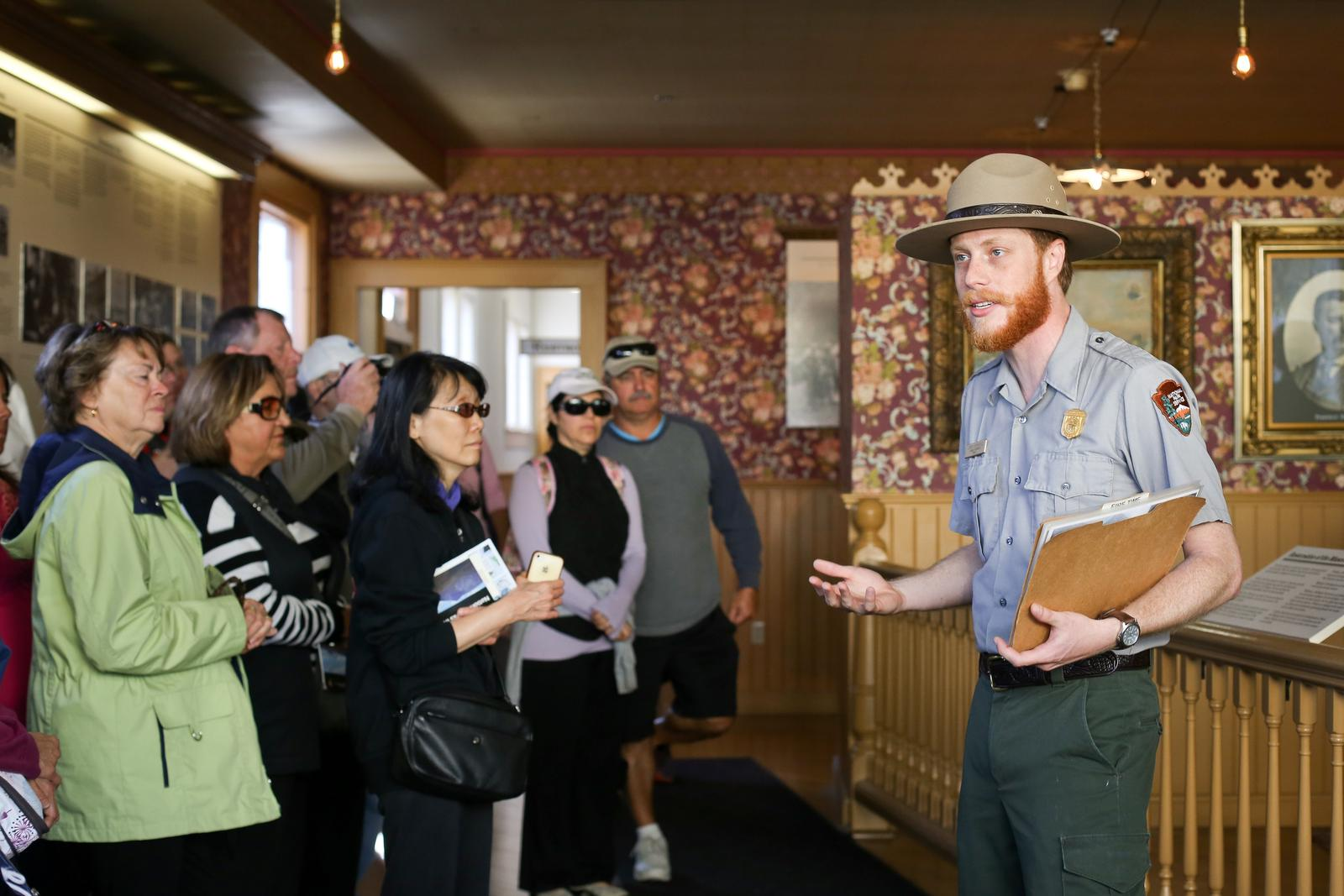 Inside a turn of the century saloon museum, a ranger talks to a group of visitors.Rangers bring the gold rush to life on walking tours through Skagway's Historic District.