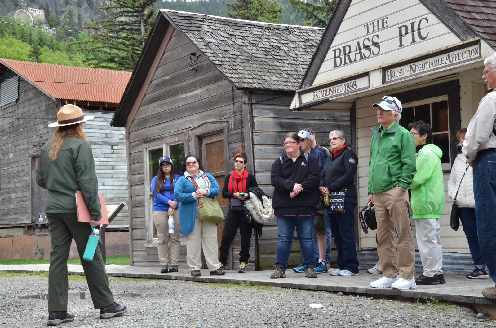 Ranger and tour group stand in front of three small historic houses.A ranger reveals the untold stories of Skagway's past.