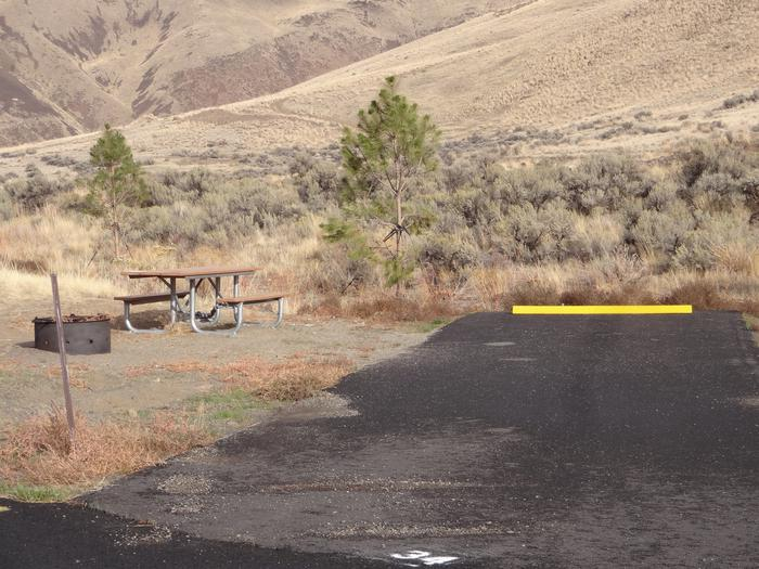 Picnic table, fire ring and parking pad at Big Pines campsite #34.Big Pines campsite #34