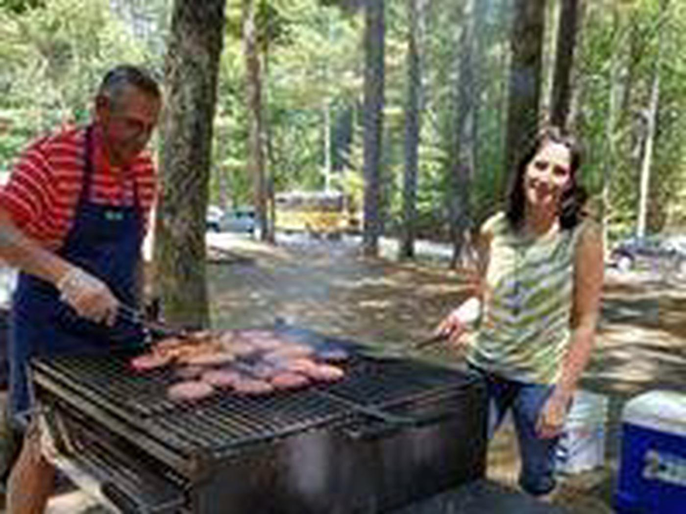 Two adults turning burgers on a large group-size park provided grill with wooded forested surrounded parking lot in background with cars and school bus.Have it your way and enjoy your gathering!