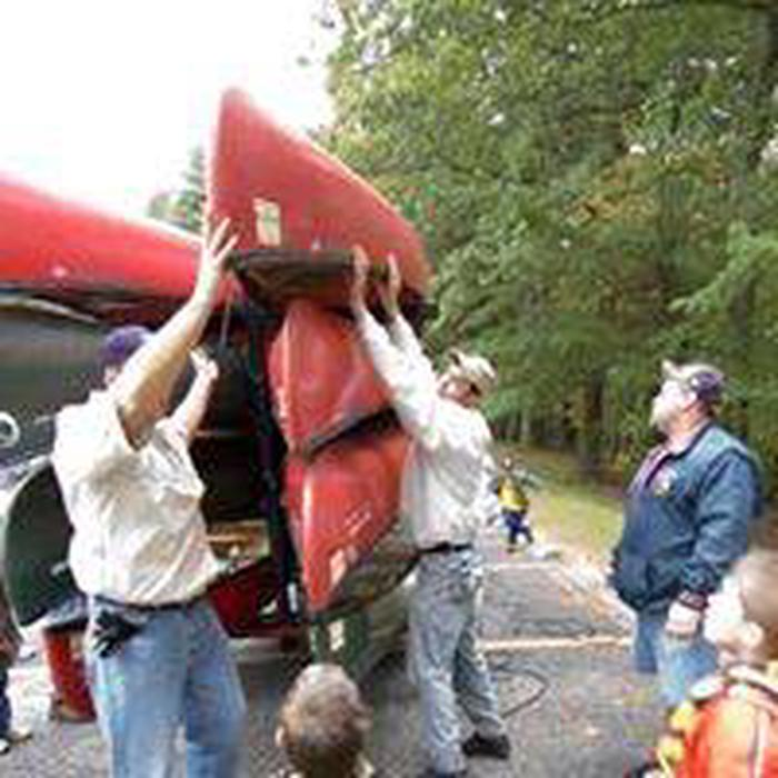 Adults and youth taking red canoes down from trailer for short walk to the Kayak/Canoe Water Trail.Kayak and canoe trail well marked and ample wetlands, parking and facilities available during the recreation season.