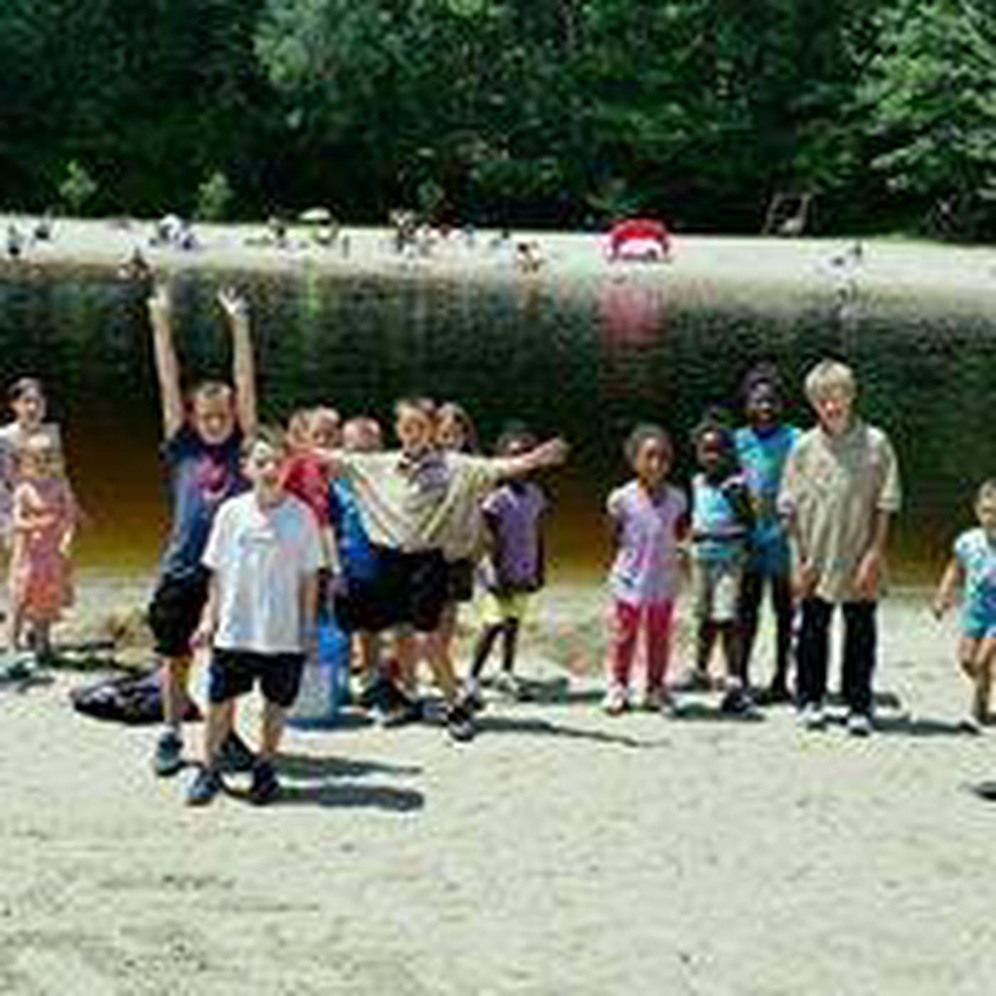 vistors of all ages, playing on both sandy beaches, open natural river swim area in the background.The water is fine . . swim time!  Bring a picnic lunch or dinner and enjoy your day!