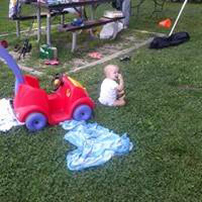 Toddler with play toys sitting on green lawn near picnic table.Room for all ages and one more car!  Enjoy your park.