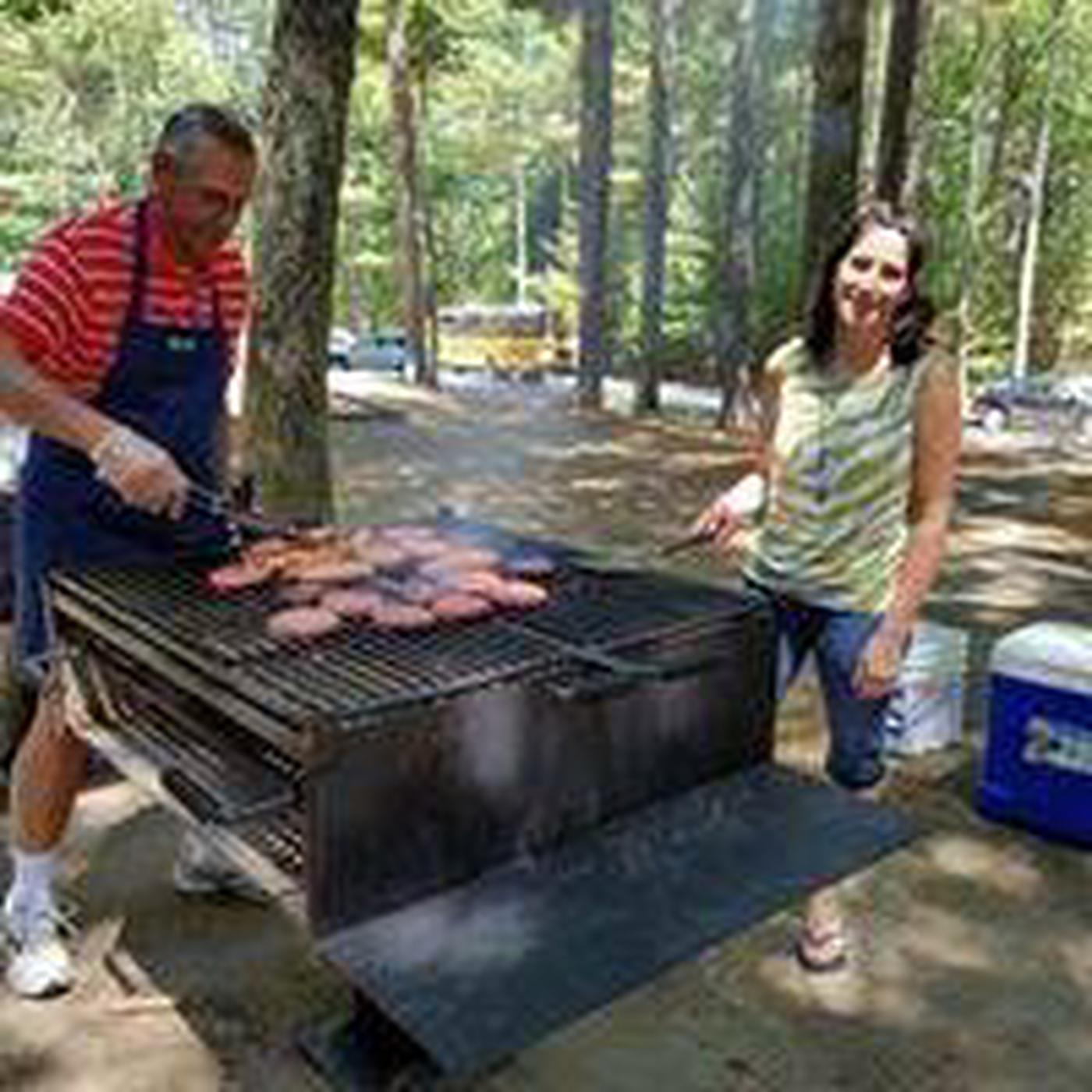 Two adults, man in apron, cooking burgers on a charcoal grill at the shelter area.  Coolers in background and forested area.Serve it your way with family and friends.  Grills provided at all shelters and picnic groves.