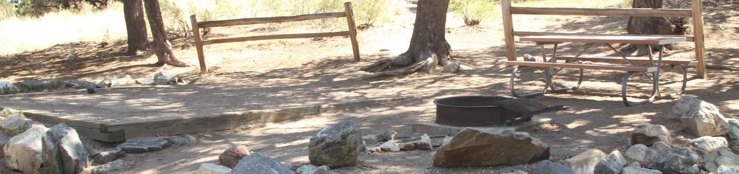 Wide view of Site #27 designated tent pad, fire ring, and picnic table. This is an out dated photo that does not show changes due to flash flood and fallen tree damage.Site #27, Pinon Flats Campground