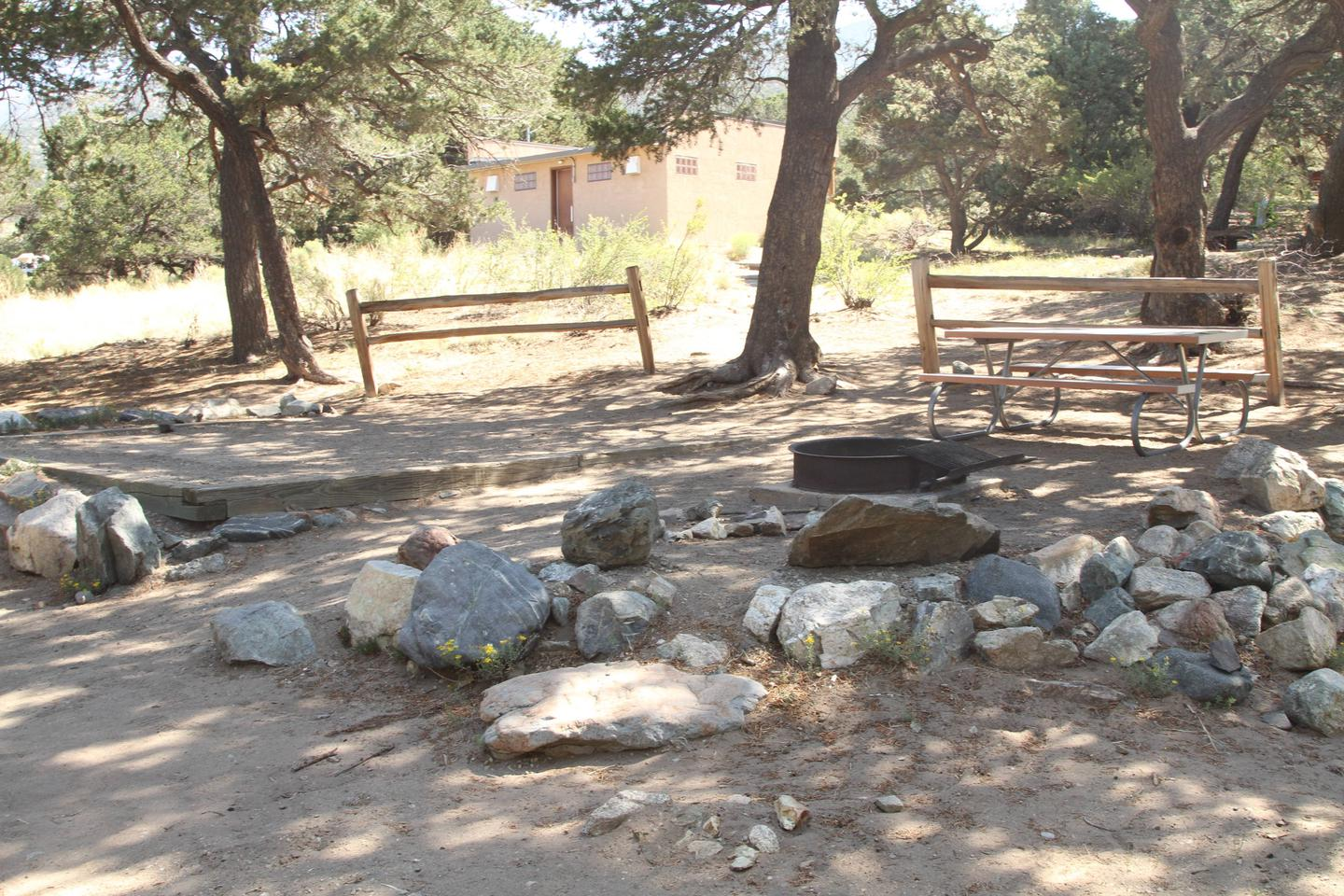 View of Site #27 designated tent pad, fire ring and picnic table. This is an out dated photo that does not show changes due to flash flood and fallen tree damage.Site #27, Pinon Flats Campground