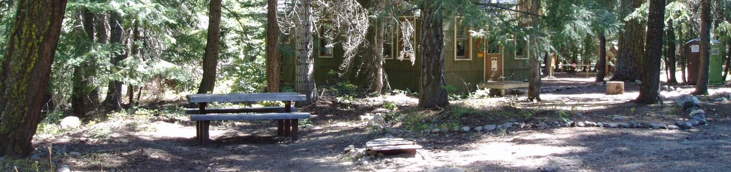 Bench in forest with cabin visible through trees in background.American River Guard Station