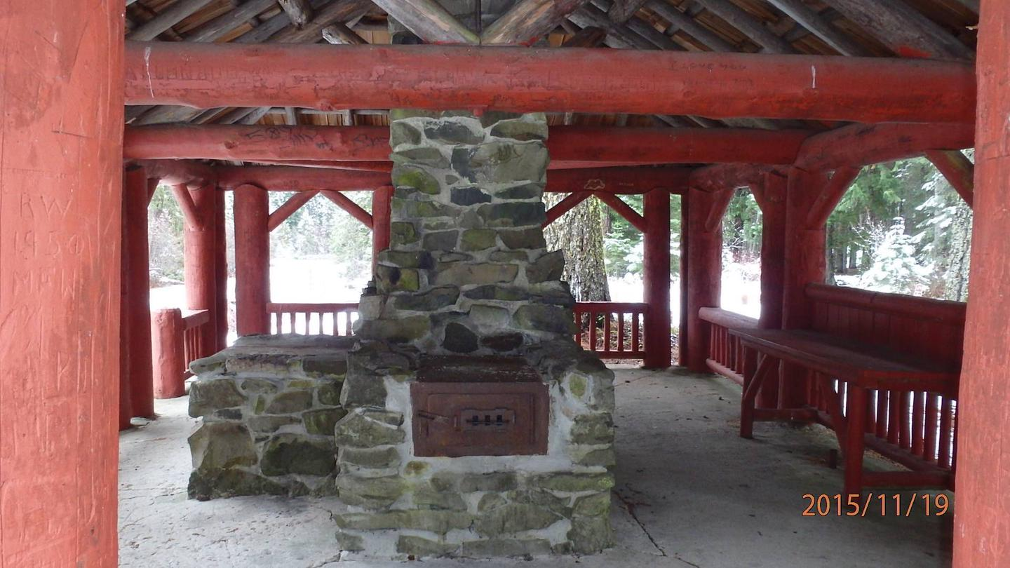 Stone fireplace and chimney next to counter under red-painted log shelter.CCC era picnic shelter