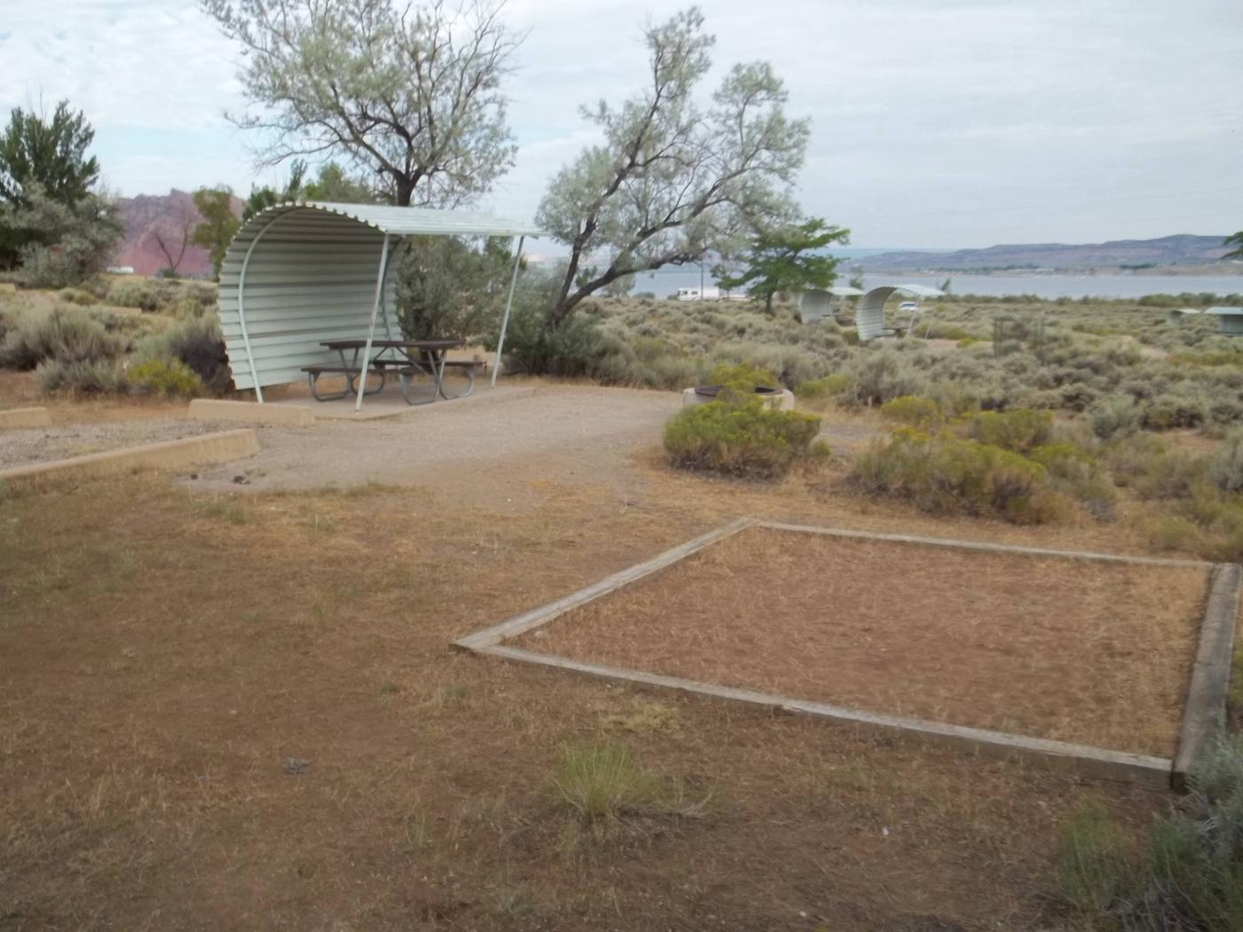 Picnic table with shelter on one side and overhead. There is a fire pit with a grill grate in front of it and a tent pad lined with timbers off to the side of the fire pit.Antelope Campground: Site 7
