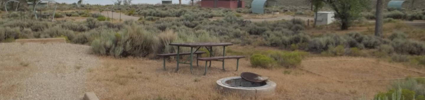 Near the picnic table, you will find a fire pit that has a grill grate. There is a tent pad lined with timbers off to the side and a red brick build that houses the restrooms is in the background.Antelope Campground: Site 9