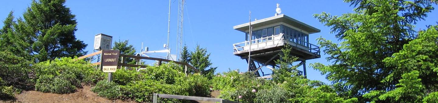 Lookout building on ridge with Forest Service i.d. sign, communications tower, green shrubs and conifer trees backed by blue sky.BALD KNOB LOOKOUT