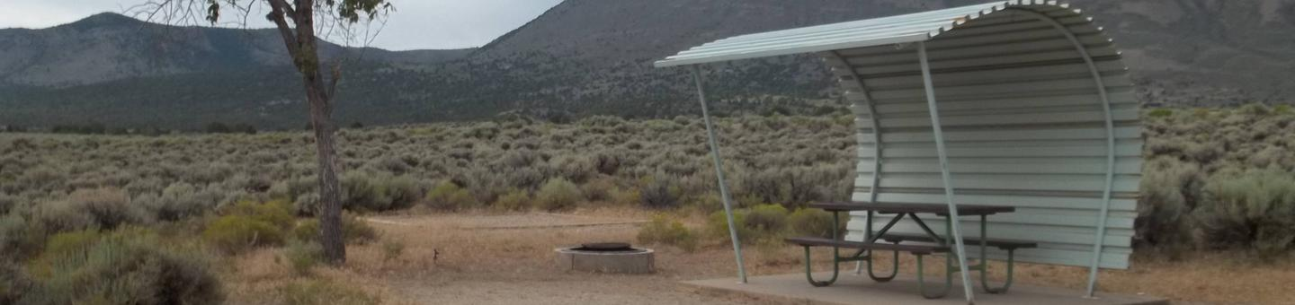 Picnic table sheltered on one side and overhead. To the side is a fire pit with a grill grate and a tent pad bordered by timbers.Antelope Flat Campground: Site 10