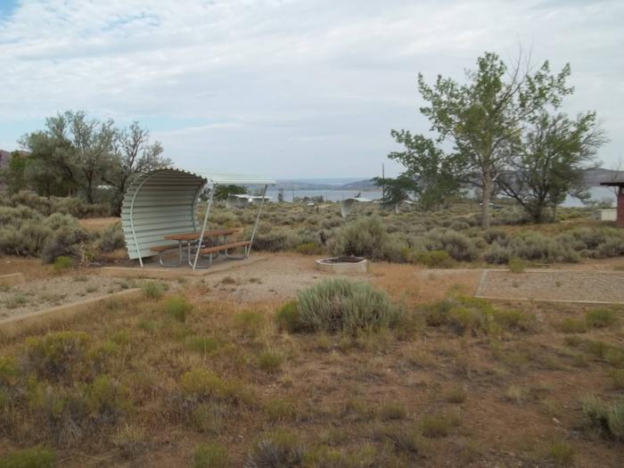 Picnic table with shelter on one side and overhead. There is a fire pit and tent pad to the side. The lake can be seen in the background.Antelope Campground: Site 11