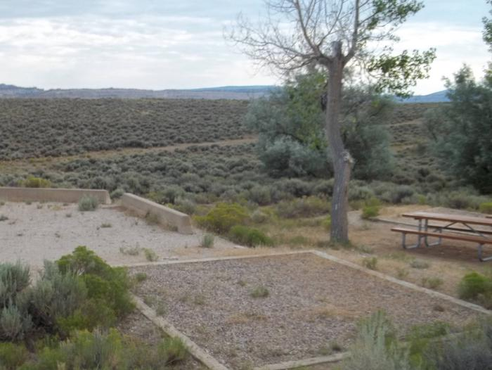 Picnic table and a timber bordered tent pad near a parking area for a campsite.Antelope Flat Campground: Site 24