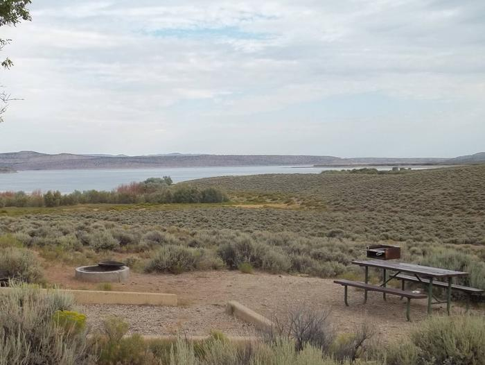 Picnic table, grill, and fire pit in a campsite surrounded by sagebrush with a lake is in the background.Antelope Flat Campground: Site 25
