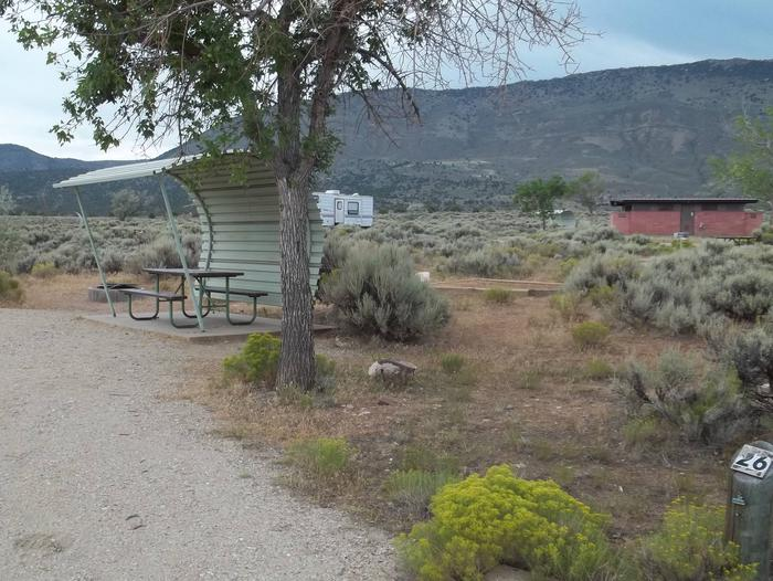 Partial sheltered picnic table with a timber border tent pad near by.  A red brick building is located in the background that houses the restrooms.Antelope Flat Campground: Site 26