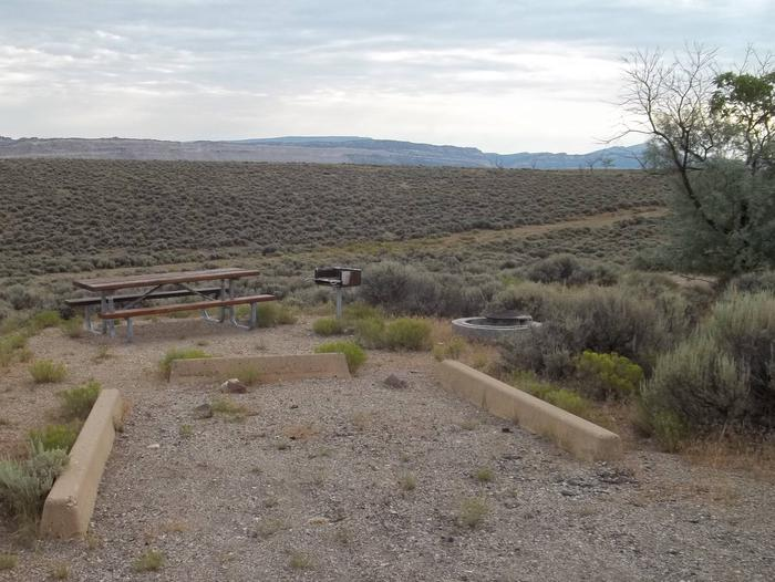 Picnic table, grill, and fire pit next to a parking lot for a campsite.Antelope Flat Campground: Site 27