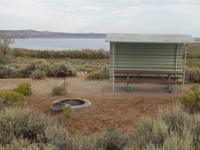 Partial covered picnic table with a lake in the background. Fire pit, grill, and tent pad are close to the picnic area.Antelope Flat Campground: Site 29