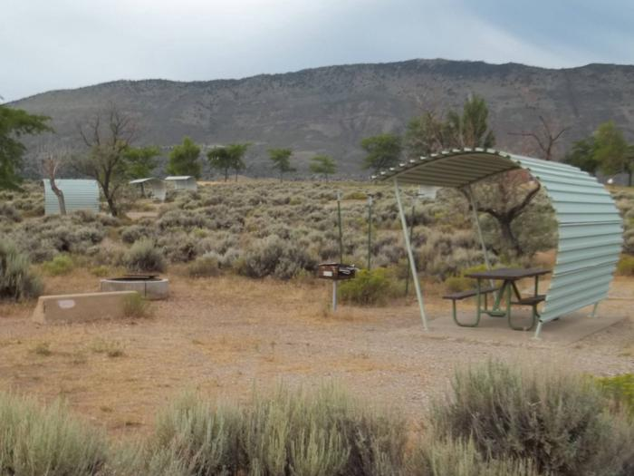 Partial covered picnic table with a grill and fire pit in a site next to a parking area. There are a number of sites in the background.Antelope Flat Campground: Site 33