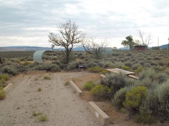 Picnic table with grill in the campsite surrounded by sagebrush. Another site and red building with restrooms is in the background.Antelope Flat Campground: Site 35