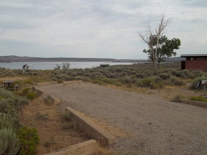 Picnic table on the side of parking strip with a grill on the other side. The lake and building with restrooms is in the background.Antelope Flat Campground: Site 41