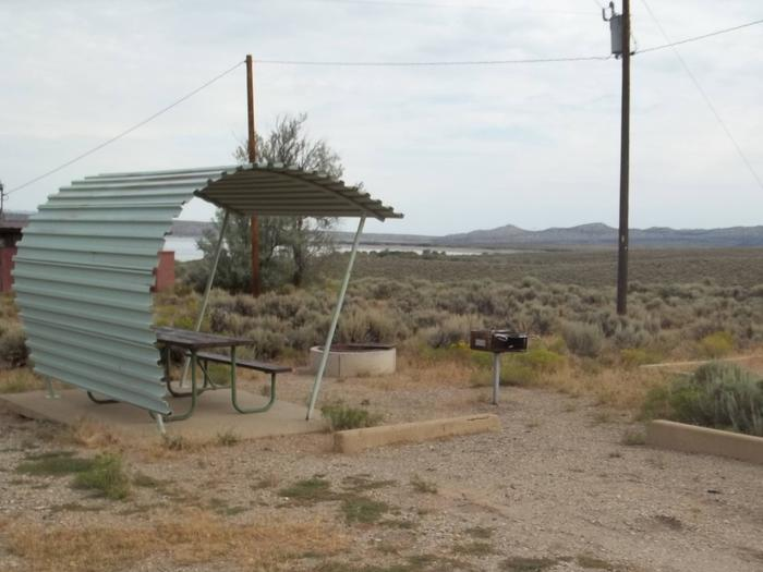 Partial covered picnic table with a grill and fire pit nearby Utility poles in the background. The lake can be seen in the far distance.Antelope Flat Campground: Site 43