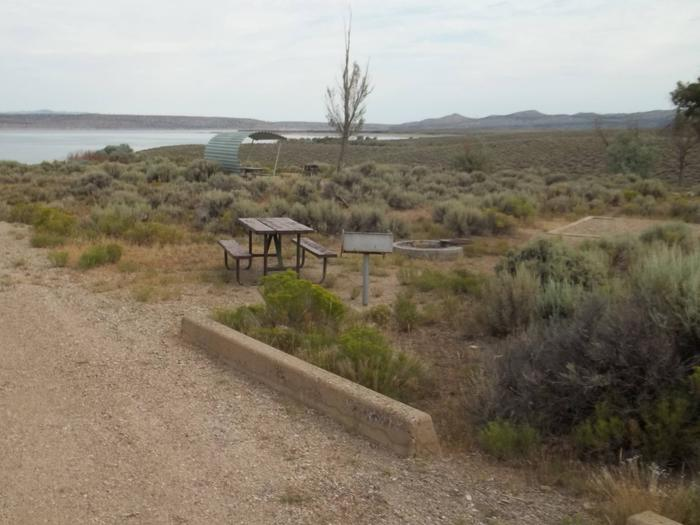 Site that has plenty of parking with picnic table, grill, fire pit, and tent pad. Another site and the lake can be seen in the background.Antelope Flat Campground: Site 44