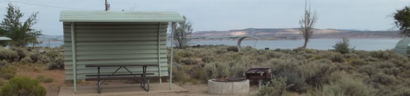 Partial covered picnic table, with grill and fire pit nearby. The lake can be seen in the background.Antelope Flat Campground: Site 46
