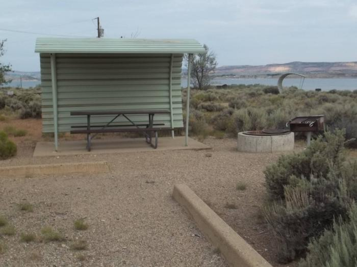 Partial covered picnic table, with grill and fire pit nearby. The lake and other campsites can be seen in the background.Antelope Flat Campground: Site 46