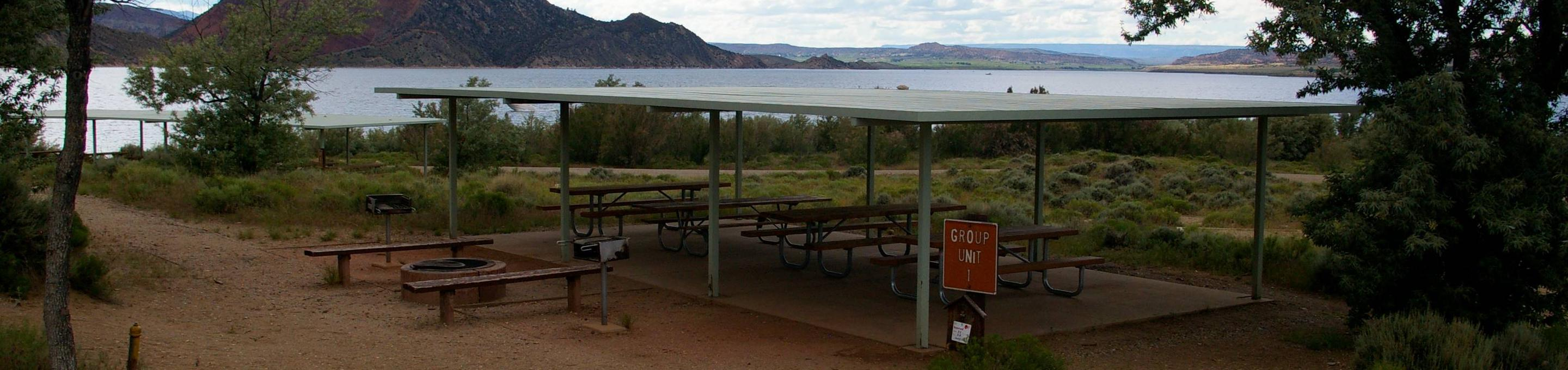 Pavillion that covers a number of picnic tables and a fire pit with some seating around it sets off to the side. The lake can be seen in the background.Antelope Flat Campground - Group Site 1