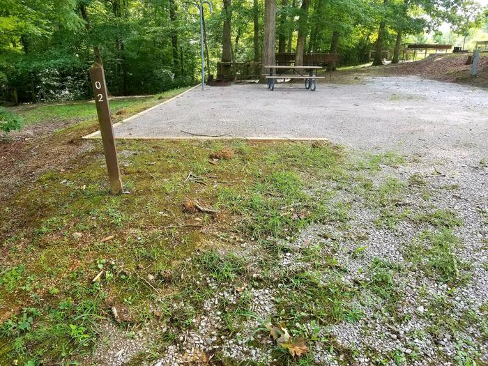 Gravel tent pad with picnic table in background near tree line.Site 2 Bear Creek Horse Camp