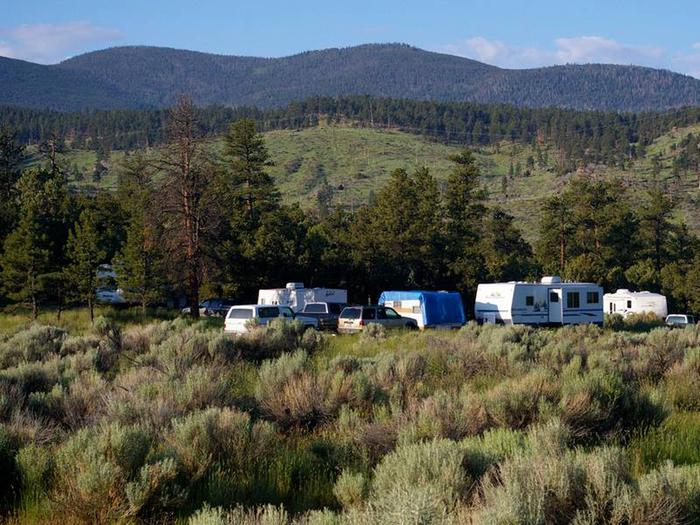 Trucks and trailers in a group campsite.Arch Dam Group Camping