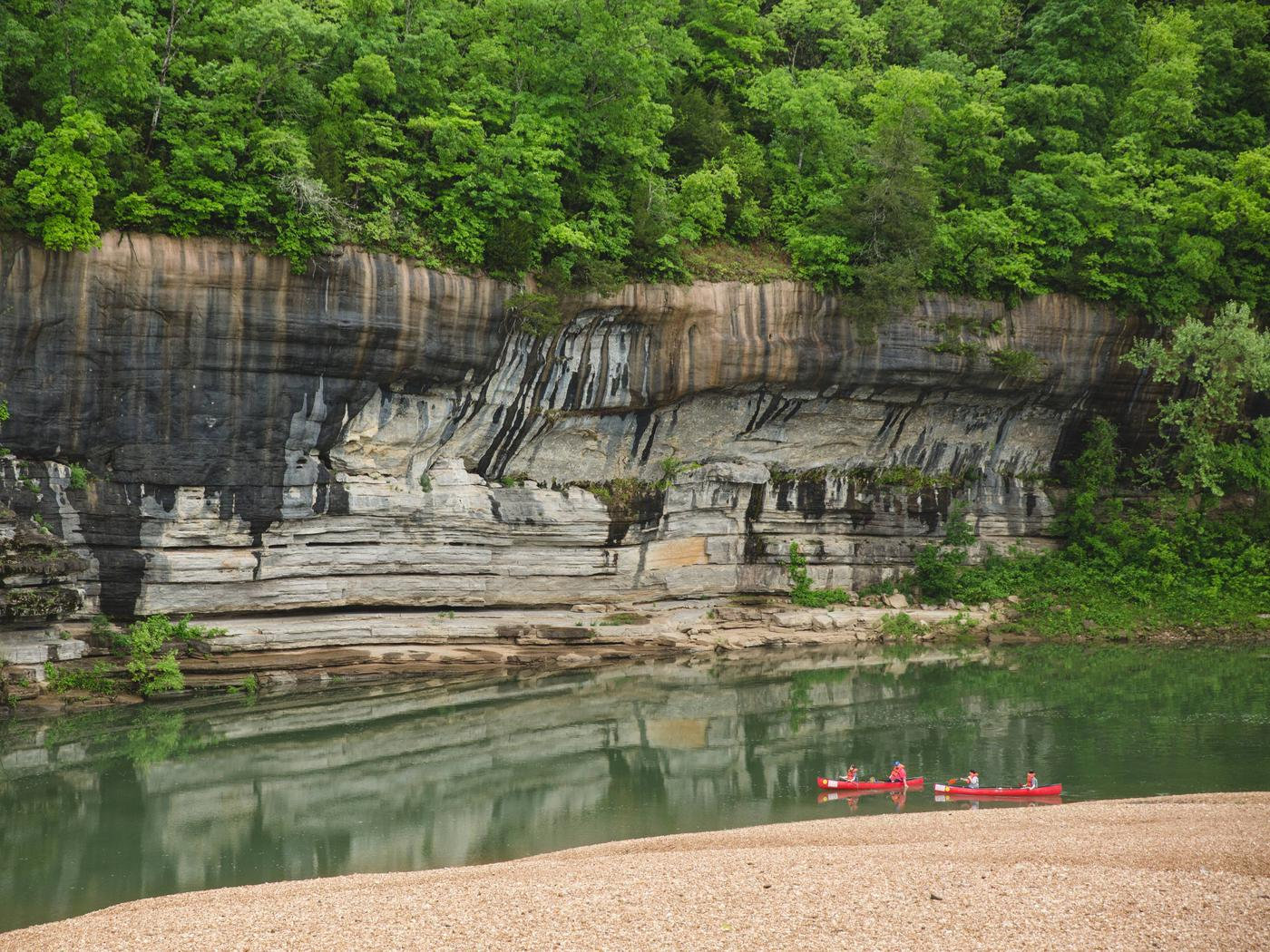 Painted Bluff at Buffalo Point with two red canoes in river.Floaters at Buffalo Point