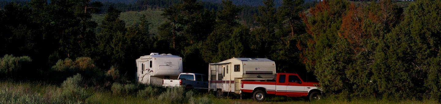 Trucks and trailers in a group campsite.Arch Dam Campground