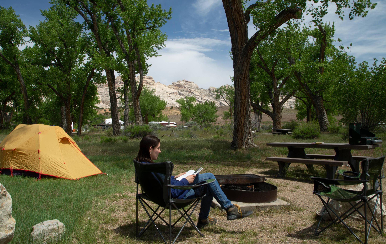 Camper in relaxing in camp chair in campsite.