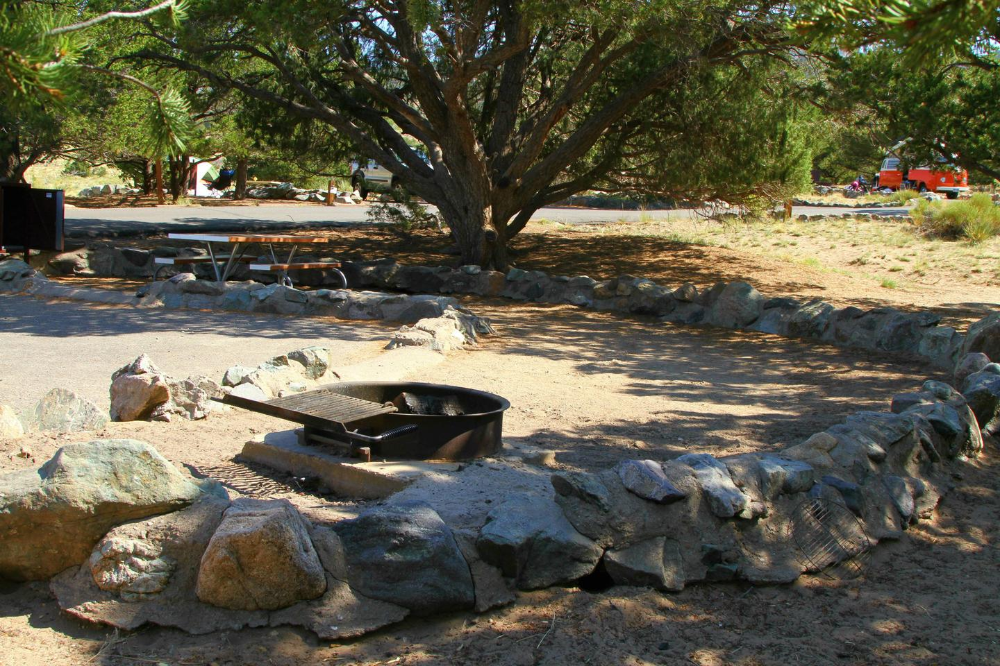 """Side view of Site #68 tent pad, with fire ring. Tent pad is not square, making an """"L"""" shape on two sides of the parking pad instead. Tent pad is bordered by a low rock wall.Site #68, Pinon Flats Campground"""