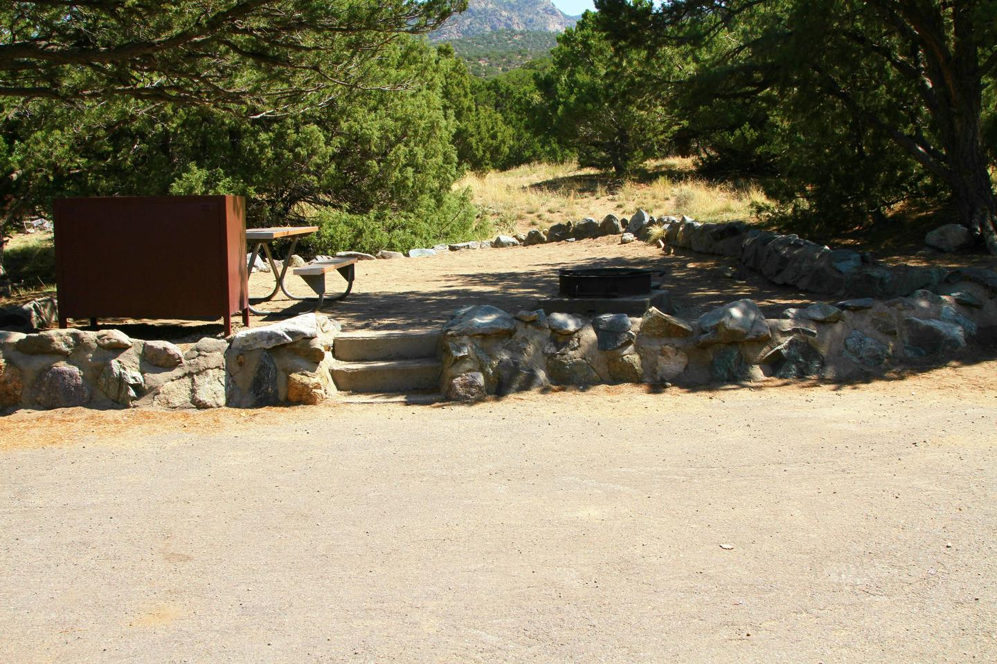 A much better picture of Site #79 tent pad with stairs going up from parking pad. Site has a low rock border and bear box, picnic table, and fire ring.Site #79, Pinon Flats Campground