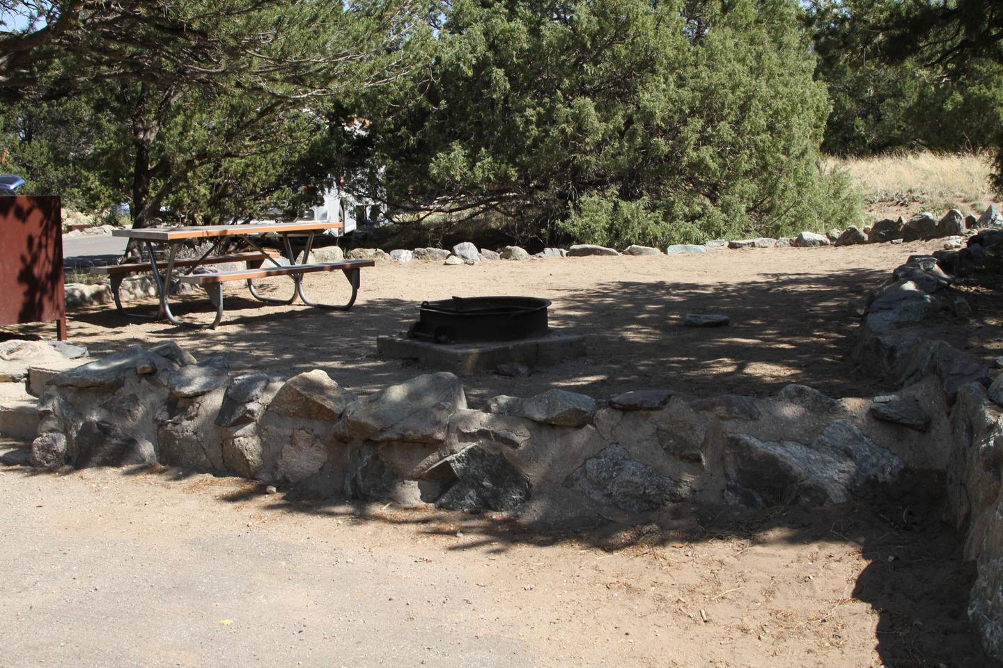 Side view of Site #79 tent pad with bear box, picnic table, and fire ring. Pine trees surround most of tent area.Site #79, Pinon Flats Campground