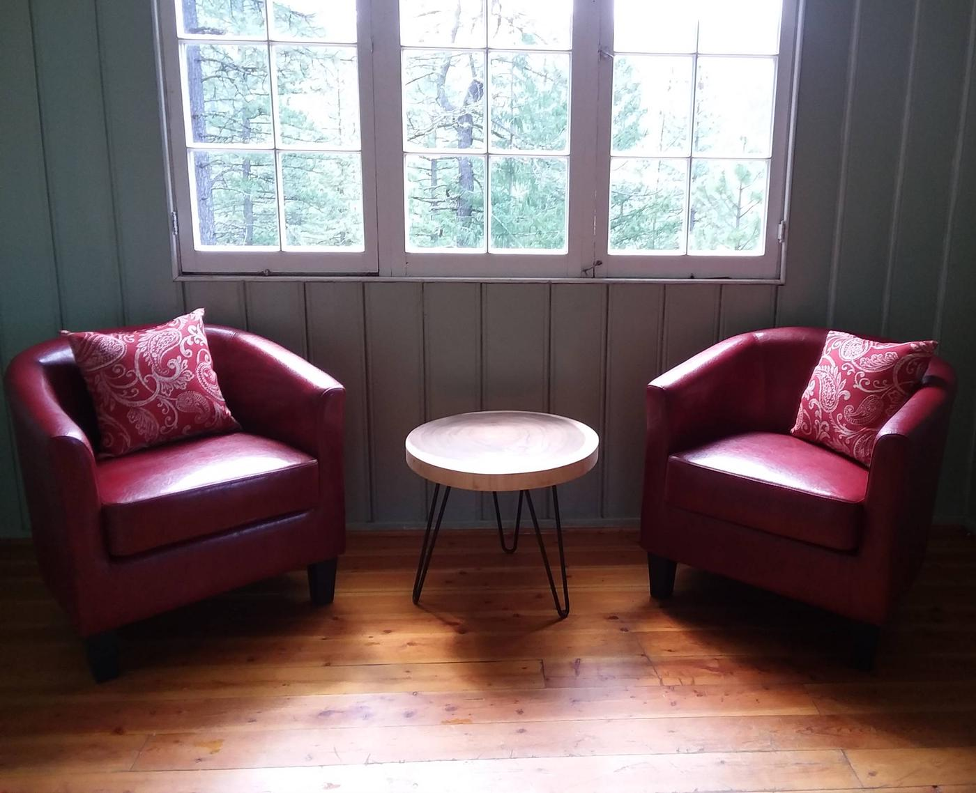 """Two red chairs and a coffee table in living room.Cozy new furniture in the living room or """"sitting"""" room."""