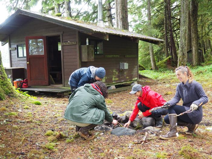 People building a fire with Harding River Cabin in backgroundExterior of Harding River Cabin
