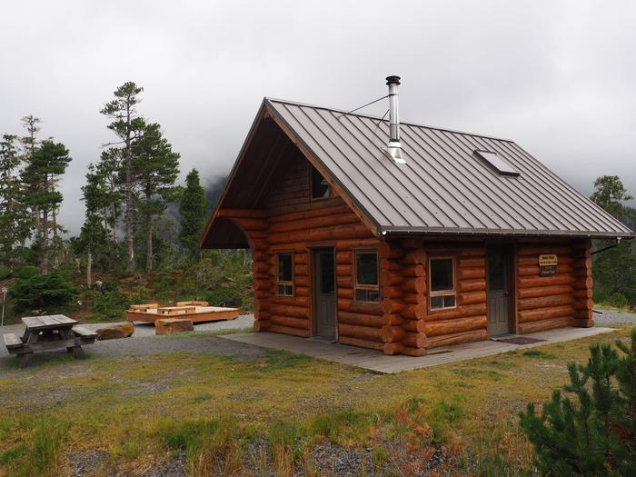 Middle Ridge Cabin with picnic table and tent platformExterior of Middle Ridge Cabin